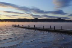 Jetty on frozen lake with vapor, hills in background at sunrise Stock Photos
