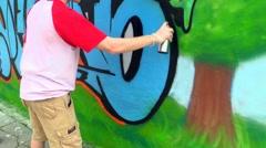 teenage boy spraying graffiti onto wall - stock footage