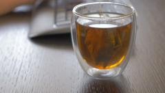 Hot cup of tea near  work place   4K 2160p UHD video - Hot glass of tea on ta Arkistovideo