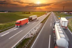 Driving trucks in motion blur on the highway at sunset Stock Photos