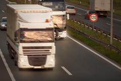 White truck in motion blur and bus on highway - stock photo