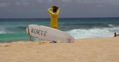 Lifeguard picks up rescue surfboard south shore Sandy Beach Oahu Hawaii Stock Footage
