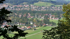 View of Hohenschwangau village framed by leaves gently blowing Bavaria, Germany Stock Footage