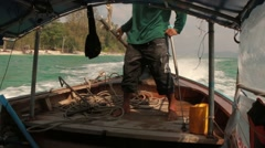 Long-tail boat pilot controls the outboard motor while driving in Ao Nang, Krabi Stock Footage
