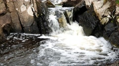 Water pooling as it flows through rocks Stock Footage