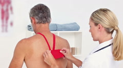 Doctor applying kinesio tape on her patients back Stock Footage