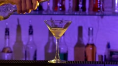 Barman pouring a liqueur and mixing alcohol liquid cocktail into glass in bar - stock footage