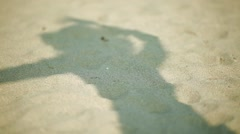 Shadow of woman on the sand as she moves around and plays with hat - stock footage