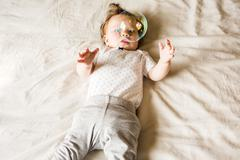 Caucasian baby girl playing with bubble on bed Stock Photos