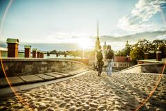 Caucasian tourists walking on cobblestone Leningrad street, Leningrad, Russia Stock Photos