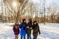 Caucasian girls arm in arm in snowy field Stock Photos