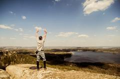 Caucasian man cheering on remote hilltop Stock Photos