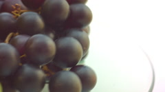 Dizzy spinning Grapes on glass table - stock footage