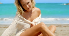 Blond Woman Wearing Light Sweater Sitting on Beach - stock footage