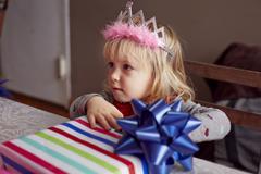 Girl wearing tiara and holding gift Stock Photos