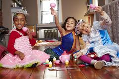 Girls playing dress-up and posing at tea party Stock Photos