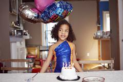 Mixed race girl with balloons and cake at party Stock Photos