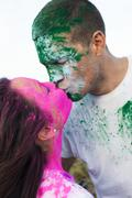 Caucasian couple splattered with paint powder kissing Stock Photos