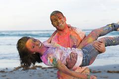 Caucasian couple splattered with paint powder on beach Stock Photos