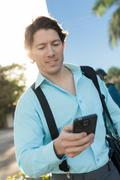 Hispanic businessman texting on cell phone outdoors Stock Photos