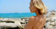 Nude Woman Enjoying View of Ocean on Rocky Beach Stock Footage