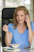 Caucasian businesswoman talking on cell phone at breakfast Stock Photos