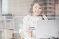 Pacific Islander woman shopping online on laptop behind window Stock Photos