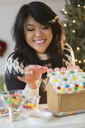 Pacific Islander woman decorating gingerbread house Stock Photos