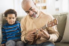 Mixed race grandfather and grandson playing ukulele Kuvituskuvat