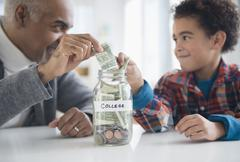 Mixed race grandfather and grandson saving money in college fund jar Stock Photos