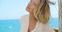 Blond Woman with Wind Swept Hair in front of Ocean - stock footage