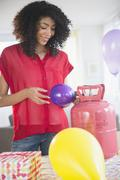 Mixed race woman inflating helium balloons for party Stock Photos