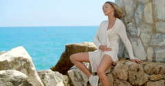 Blond Woman Sitting by Ocean Front Stone Wall Stock Footage
