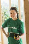 Mixed race volunteer helping build house Stock Photos
