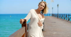 Blond Woman in White Cover Up Standing on Pier Stock Footage