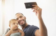 Father taking cell phone photograph with baby son Kuvituskuvat