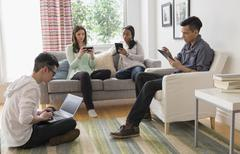 Friends using technology in living room Stock Photos