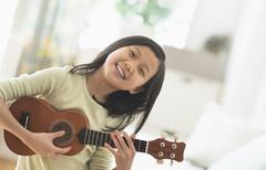 Chinese girl practicing ukulele in bedroom Kuvituskuvat