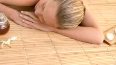 Woman enjoying a herbal compress massage - stock footage