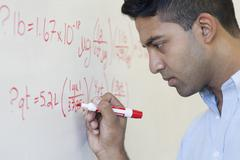 Asian businessman writing formula on whiteboard Stock Photos