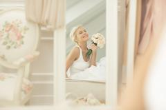 Smiling bride admiring herself in mirror on bed Stock Photos
