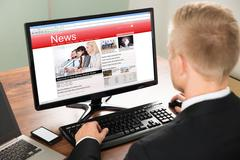 Close-up Of A Businessman Reading News On Computer At Office Stock Photos