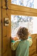 Caucasian boy looking out door window Stock Photos