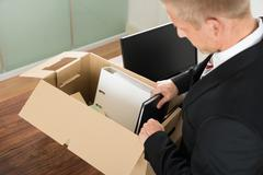 Close-up Of A Businessman Packing Files In Cardboard Box At Office Stock Photos