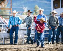 Cowboys watching boy throw lasso in rodeo Kuvituskuvat