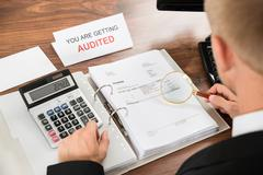 Close-up Of A Male Auditor Checking Invoice Using Magnifying Glass And Calcul Stock Photos