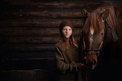 Caucasian girl standing with horse in barn Stock Photos