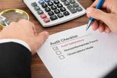 Close-up Of A Person's Hand Filling Audit Checklist Form Stock Photos