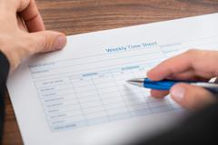Close-up Of Person's Hand Filling Blank Weekly Time Sheet With Pen Stock Photos