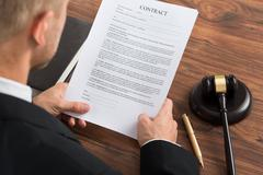 Close-up Of Judge Reading Contract Paper At Desk In Courthouse - stock photo